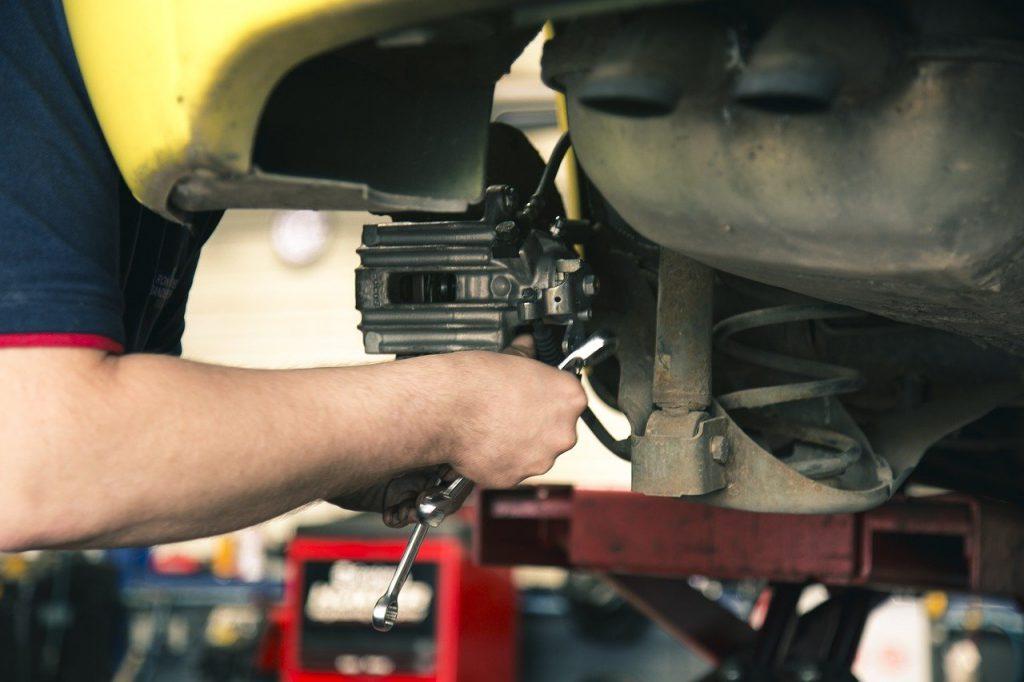 mechanik przy naprawie hamulców